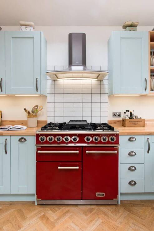 new u-shaped kitchen with pale blue shaker doors and red rangecooker