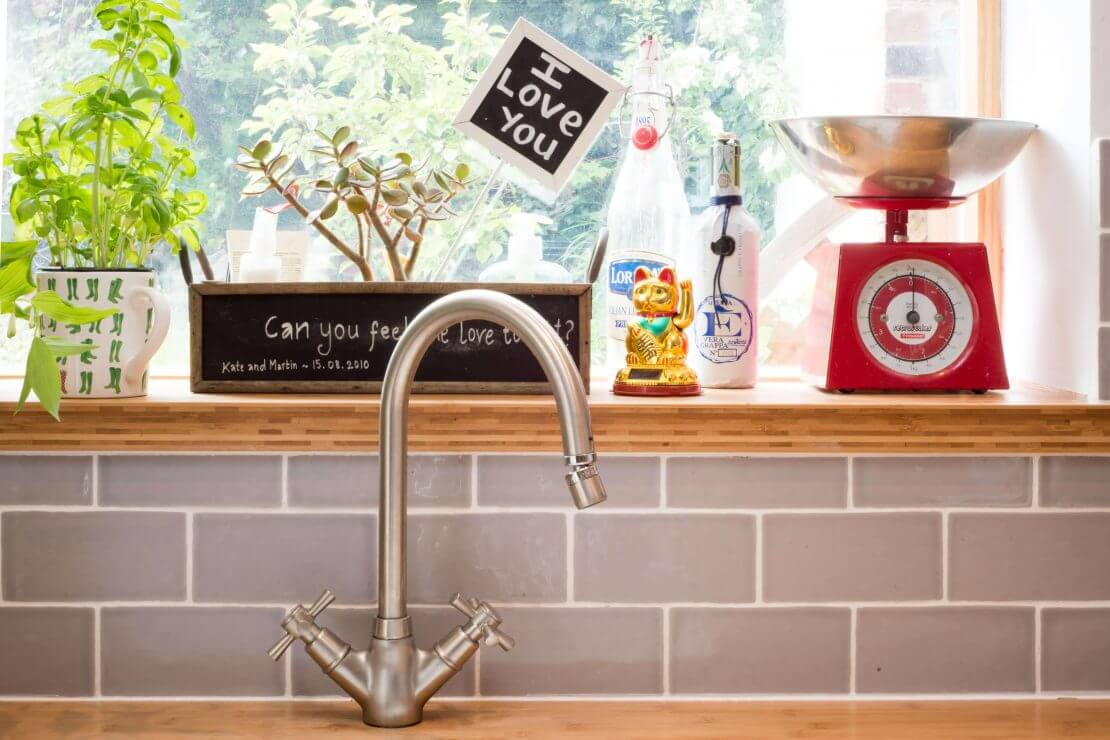 bamboo windowsill and stainless steel tap in new compact kitchen