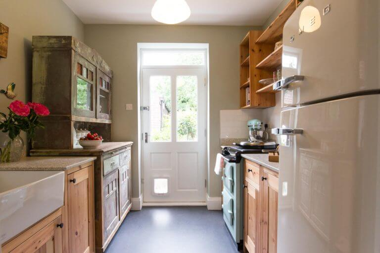new compact galley kitchen with pine cupboards