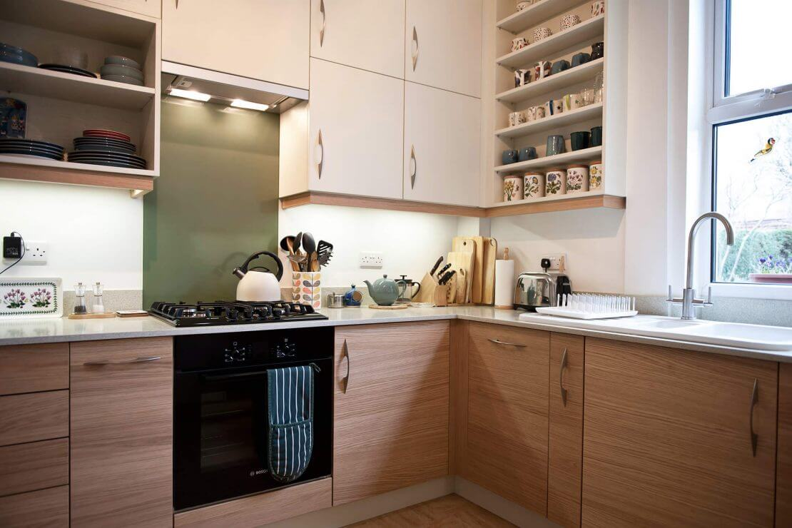 new L-shaped kitchen with flat panelled doors and glass splashback