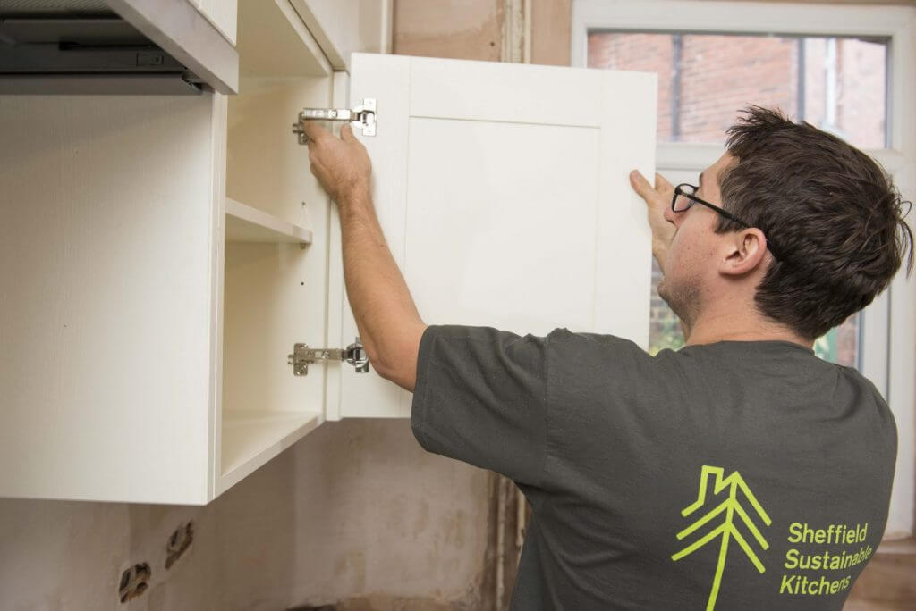 kitchen fitter fixing kitchen cabinet hinge on site in open cupboard