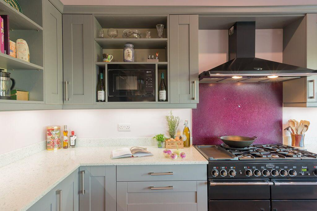 pale blue shaker kitchen with recycled glass worktops and purple splashback behind large range cooker