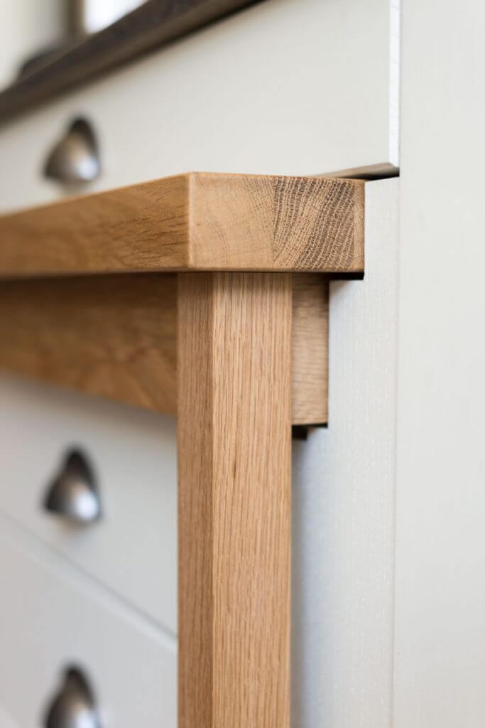 close up of solid oak timber kitchen table pushed in to recess
