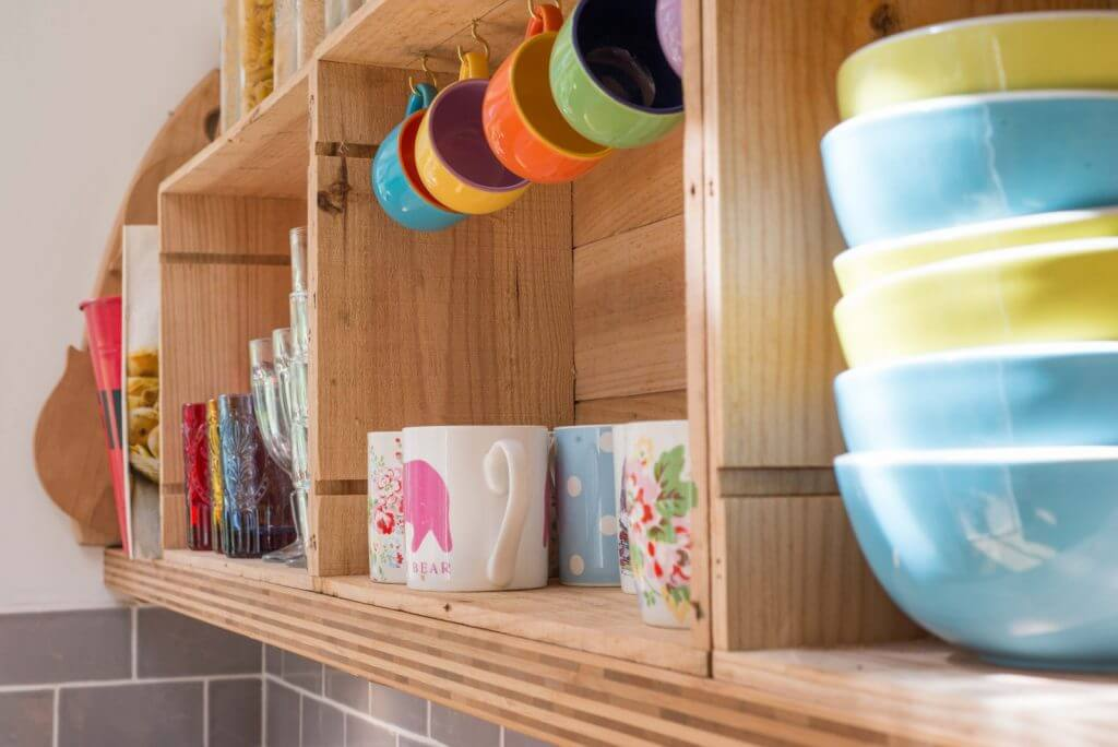 close up of kitchen shelves made for wine boxes with crockery
