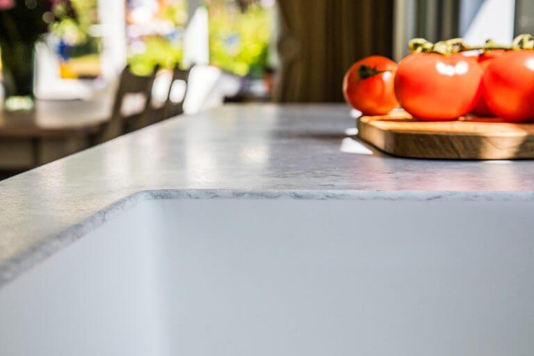 close up of integral kitchen sink and worktop with tomatoes