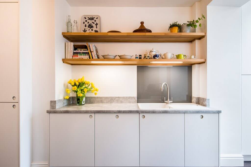 scandi-style white kitchen with slab kitchen cabinet doors with circular cut-out pull handles and ceramic sink