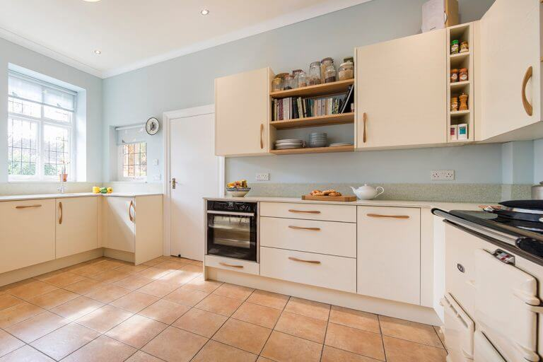 large bright kitchen with cream slab painted timber cabinet doors and oak features