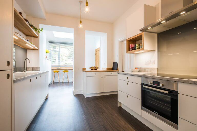 scandi kitchen with white slab doors and grey laminate worktops