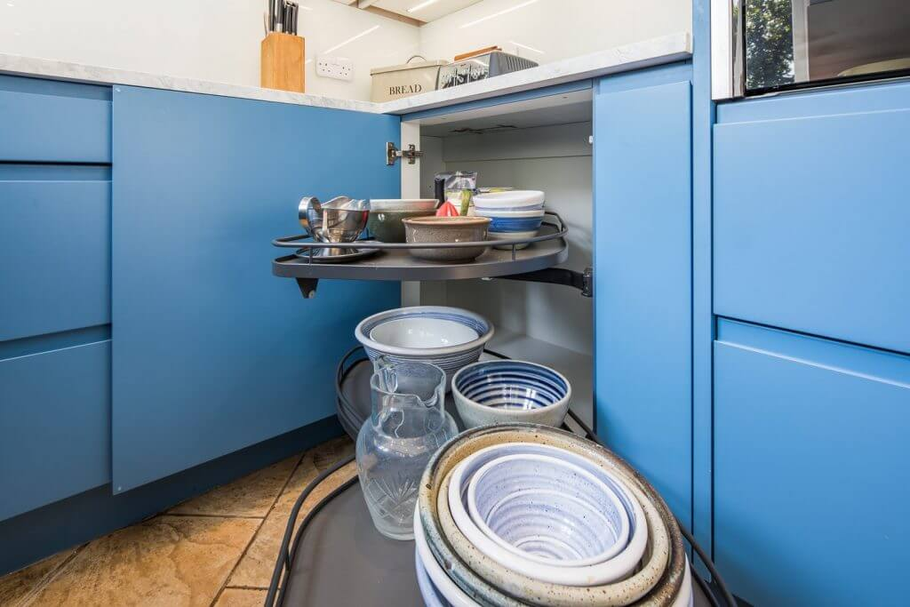 blue kitchen cabinets open to reveal contents of corner cupboard and pullout storage unit