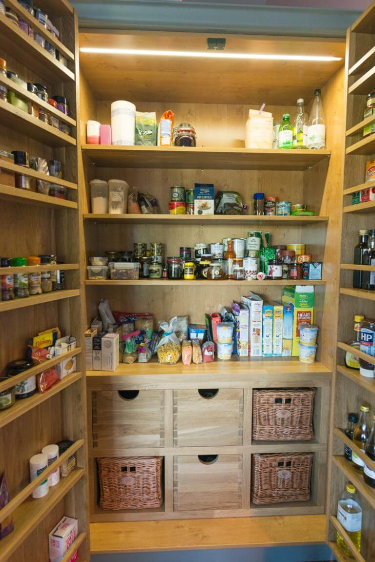 full height kitchen pantry larder open to show food and jars tins and kitchen supplies