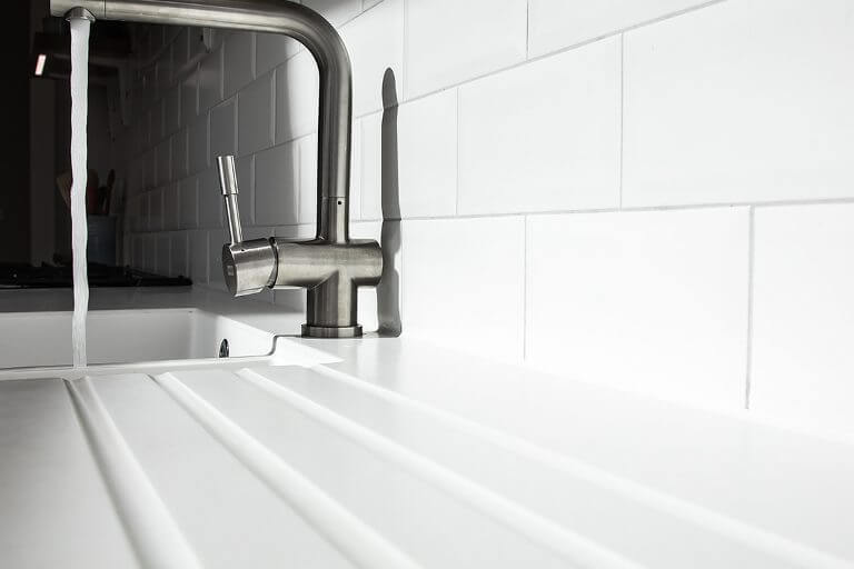 close up of white integral acrylic sink and drainer grooves