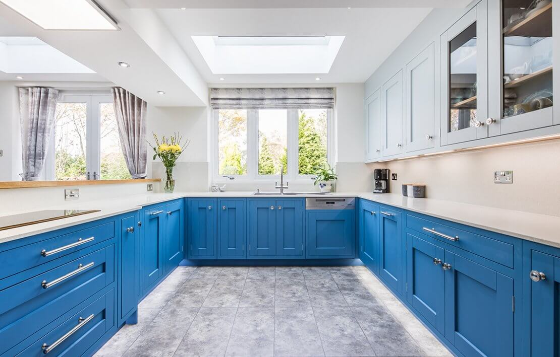 large blue u-shaped kitchen with lots of light and huge window above sink