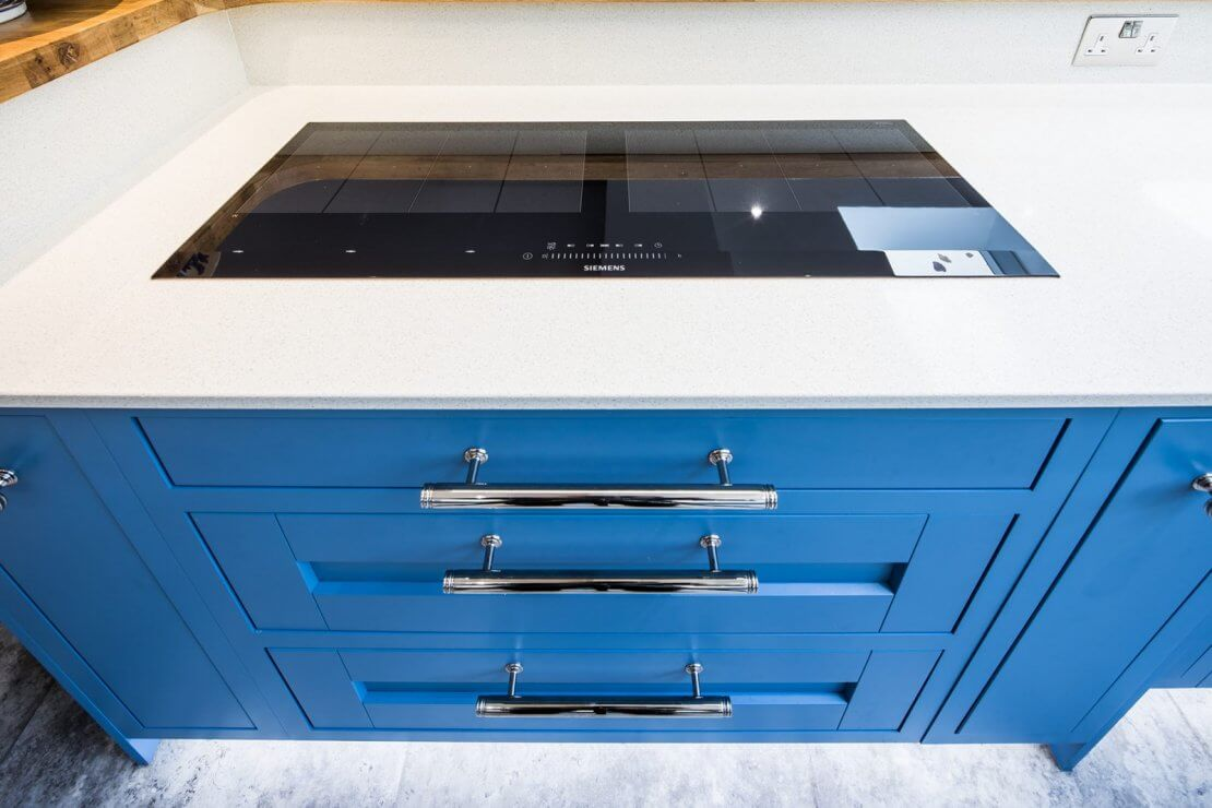 dark blue kitchen drawers and recycled glass worktop