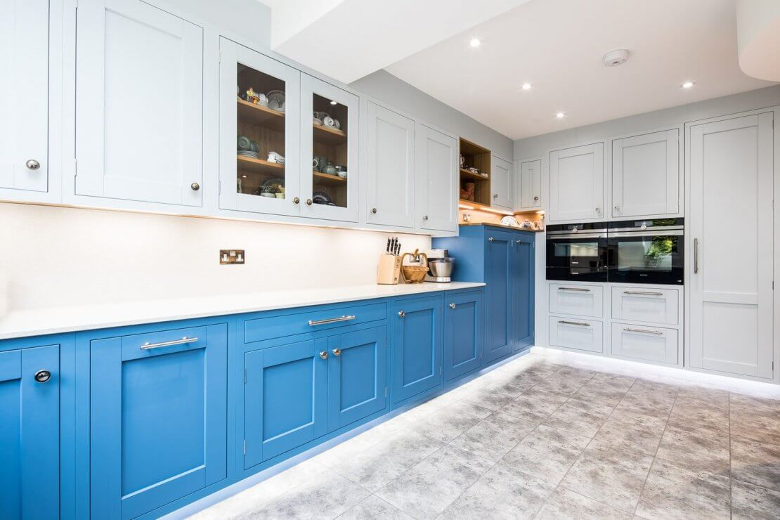 large kitchen with dark blue floor cabinets and pale blue wall cabinets