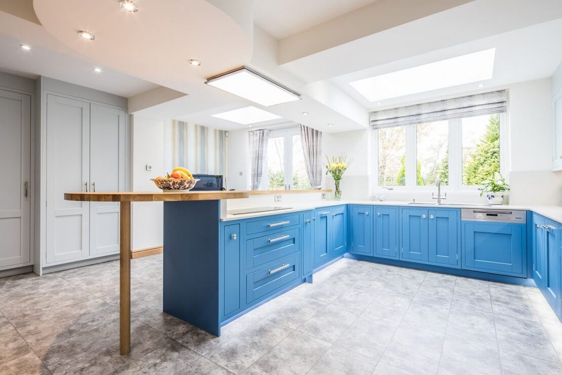 large u-shaped blue kitchen with wooden breakfast bar
