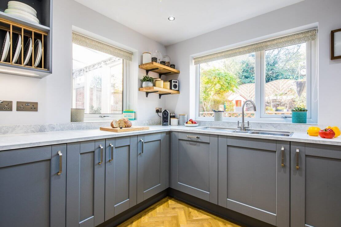 grey painted shaker u-shaped kitchen with stainless steel sink and oak open shelving