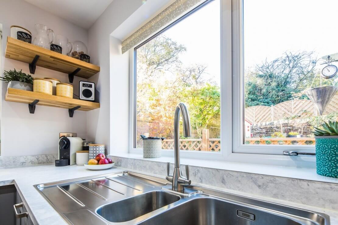 stainless steel sink and tap in from of kitchen window