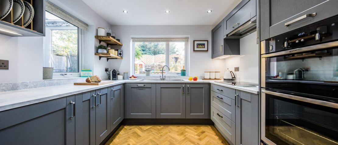 New u-shaped kitchen with painted grey shaker cupboard doors and wood effect floor