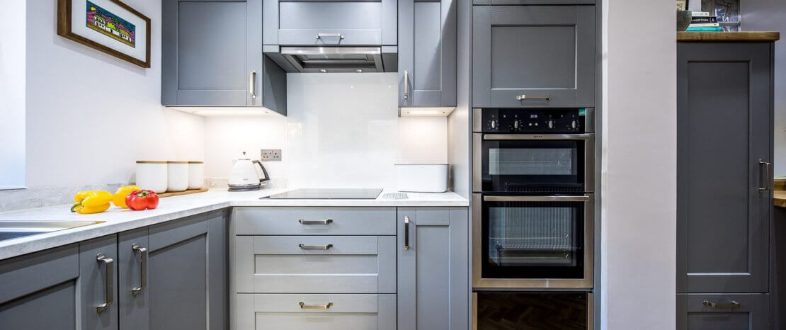 grey painted shaker new u-shaped kitchen with double oven and induction hob