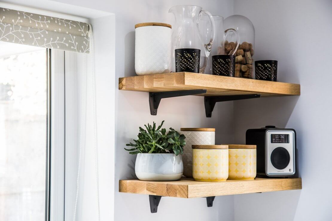 close p of oak timber open shelves housing ceramic kitchen pots and plant and radio