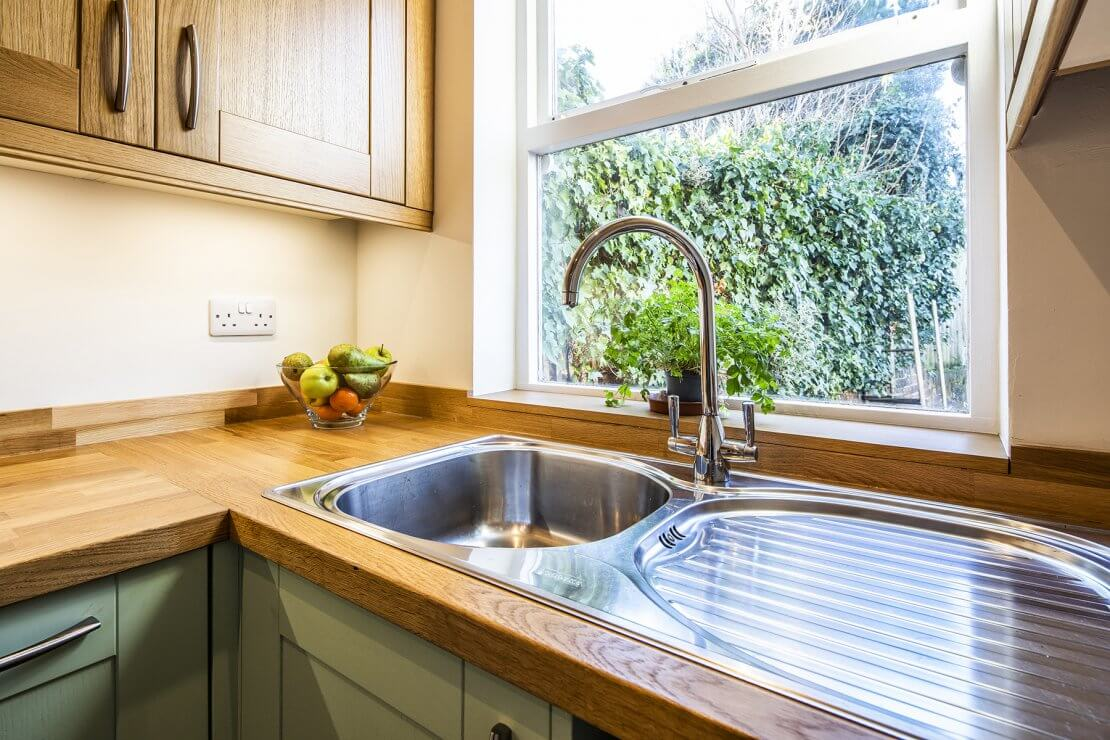 Sheffield Sustainable Kitchens oak and green compact kitchen with stainless steel sink