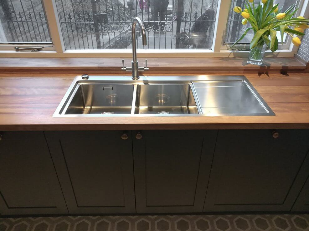 minimalist galley kitchen with timber worktop and stainless steel inset sink