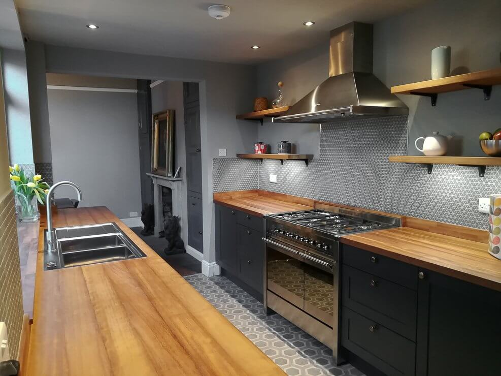minimalist galley kitchen with timber worktops and dark painted cabinet doors