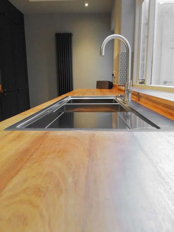 minimalist galley kitchen with timber worktops and stainless steel inset sink