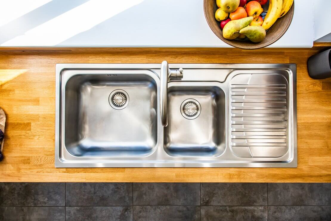 stainless steel sink and tap in new u-shaped kitchen with oak worktop