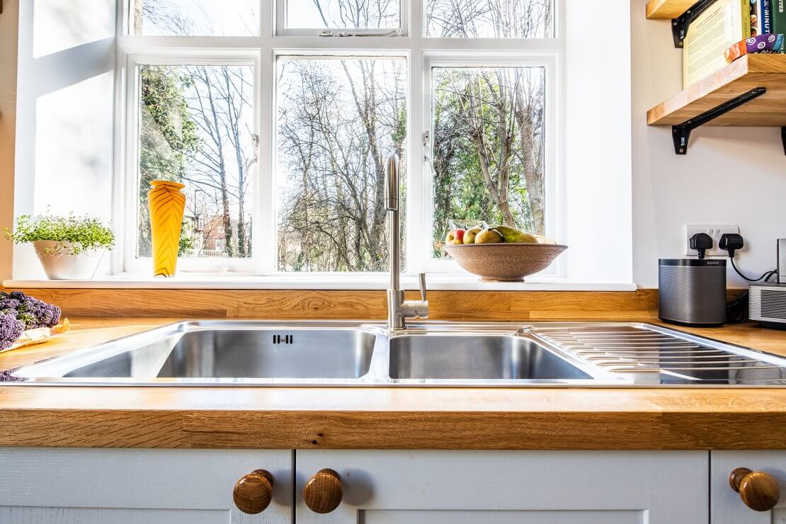 stainless steel sink in new u-shaped kitchen with shaker cabinets and oak worktop