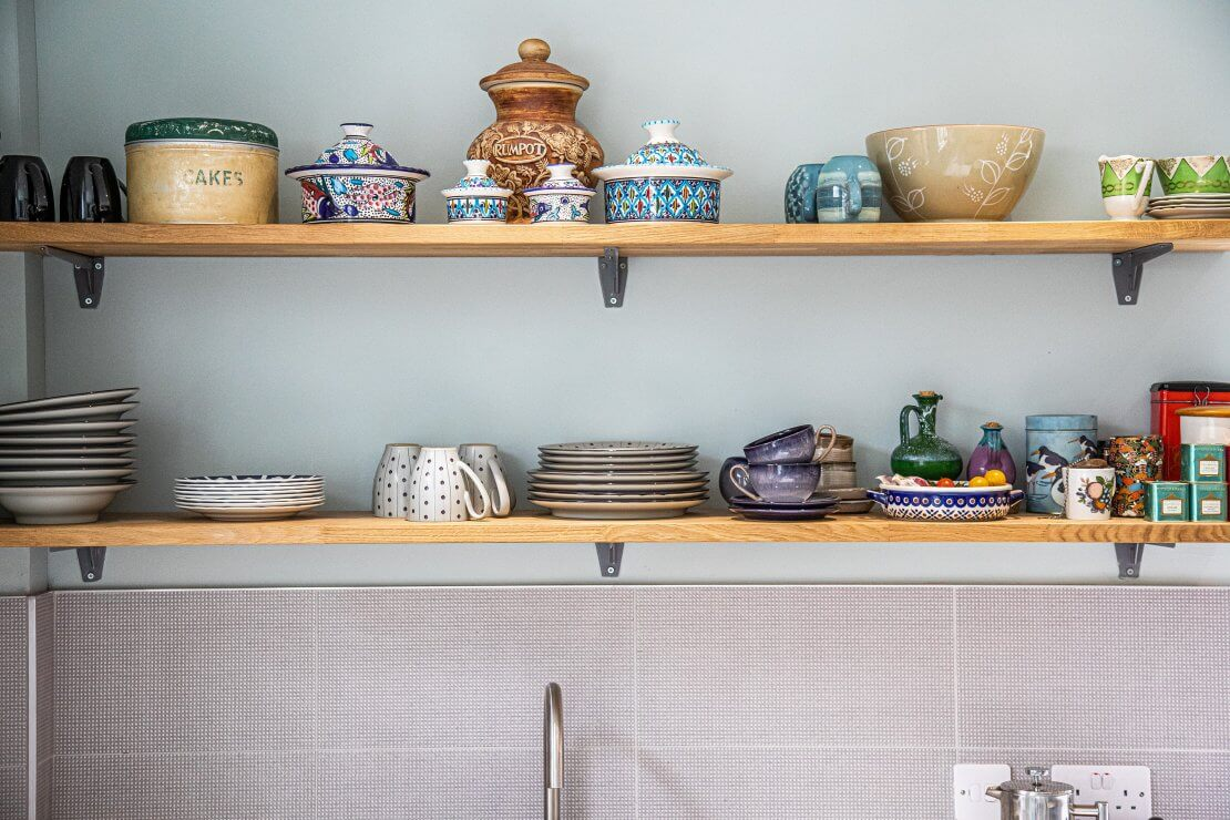 open shelves with kitchen crockery in sustainable kitchen