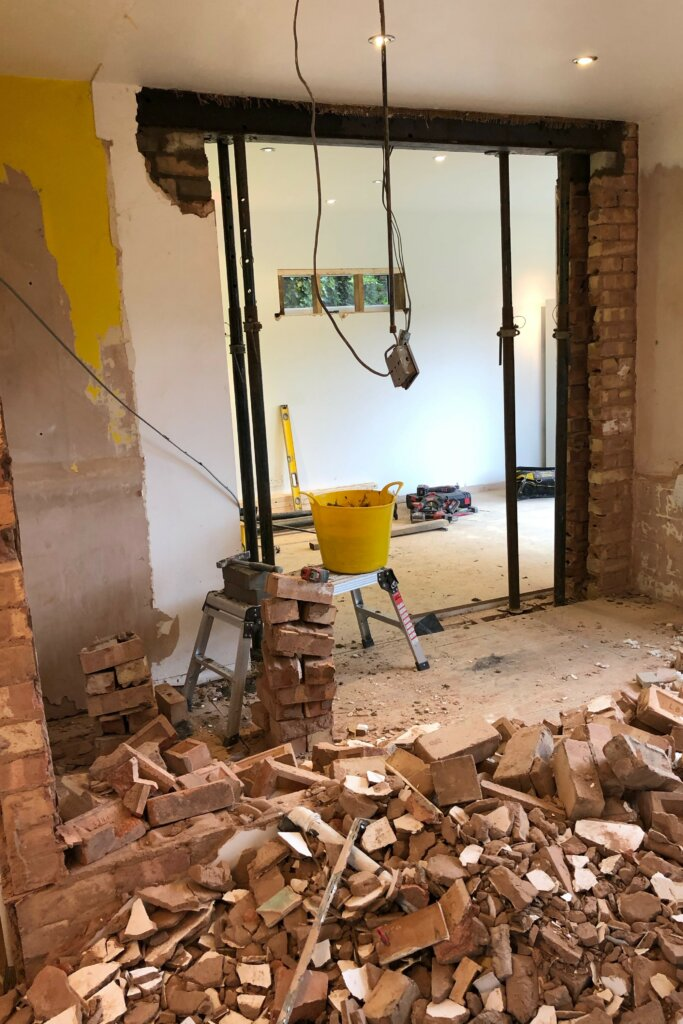 building work knocked through wall with bricks on the floor of kitchen