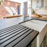 traditional shaker kitchen with recycled paper worktop on kitchen island and belfast sink