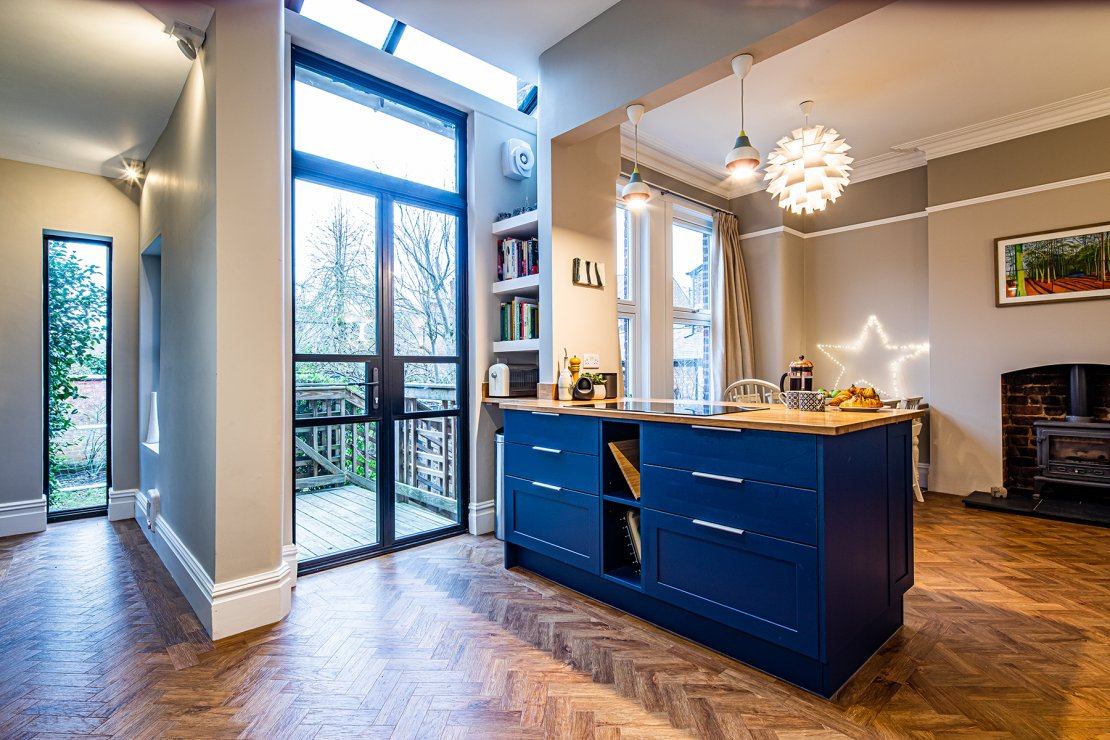 Manchester sustainable living kitchen with two tones of blue shaker doors ad oak and recycled glass worktops