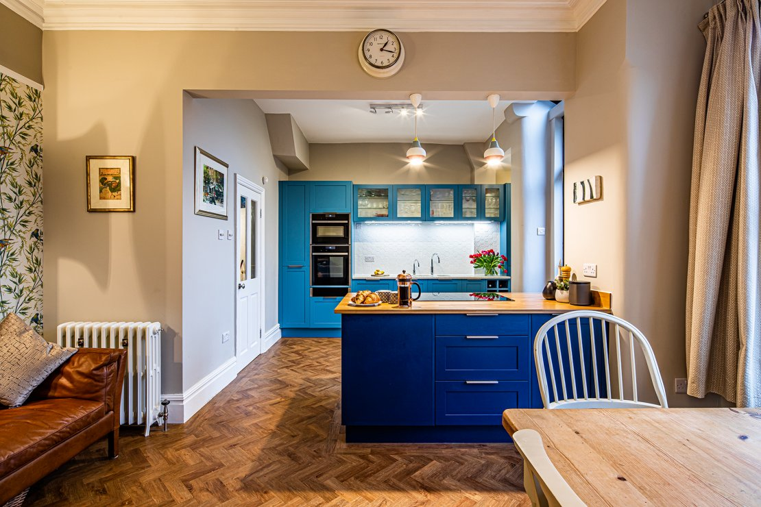 Manchester sustainable kitchen with two tones of blue shaker doors ad oak and recycled glass worktops