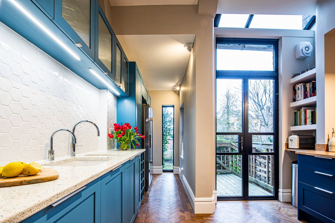 narrow small blue kitchen with ceiling to floor windows