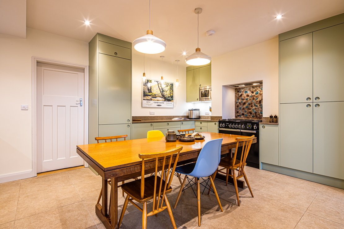 green kitchen with slab doors and oak dining table