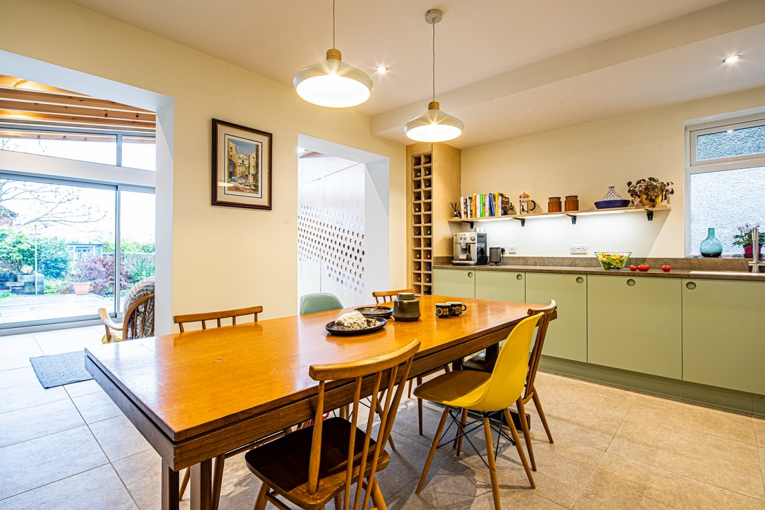 green and white kitchen with oak table