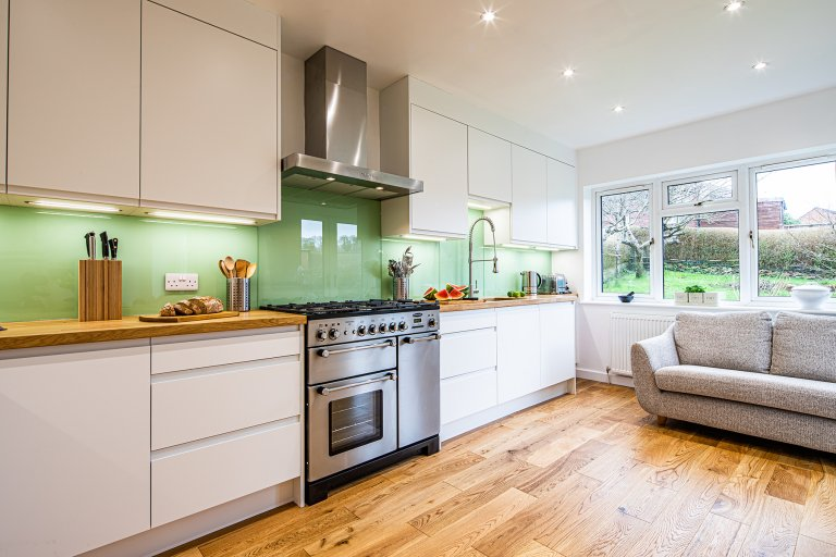 bespoke white kitchen with green glass