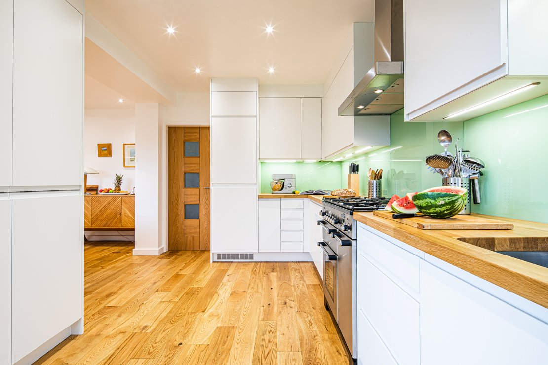 L-shaped white kitchen with green glass