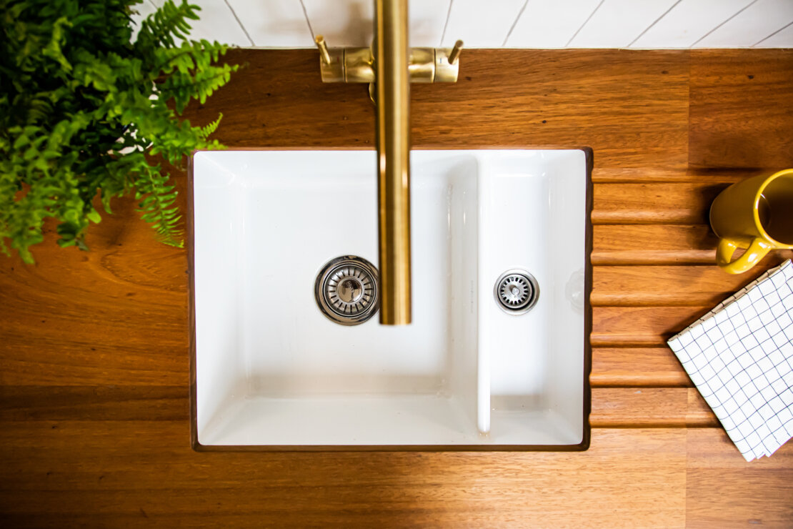 iroko worktop with drainer grooves and brass tap