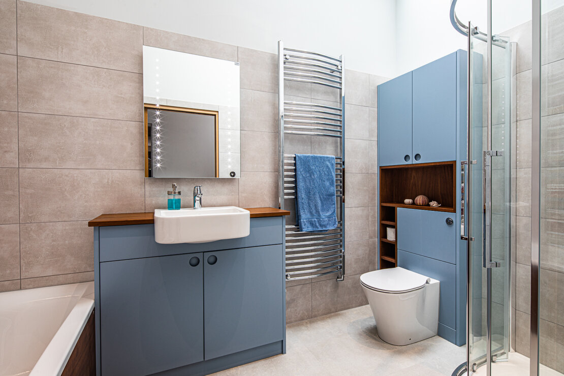 Bathroom with grey wall tiles and bespoke blue toilet storage unit