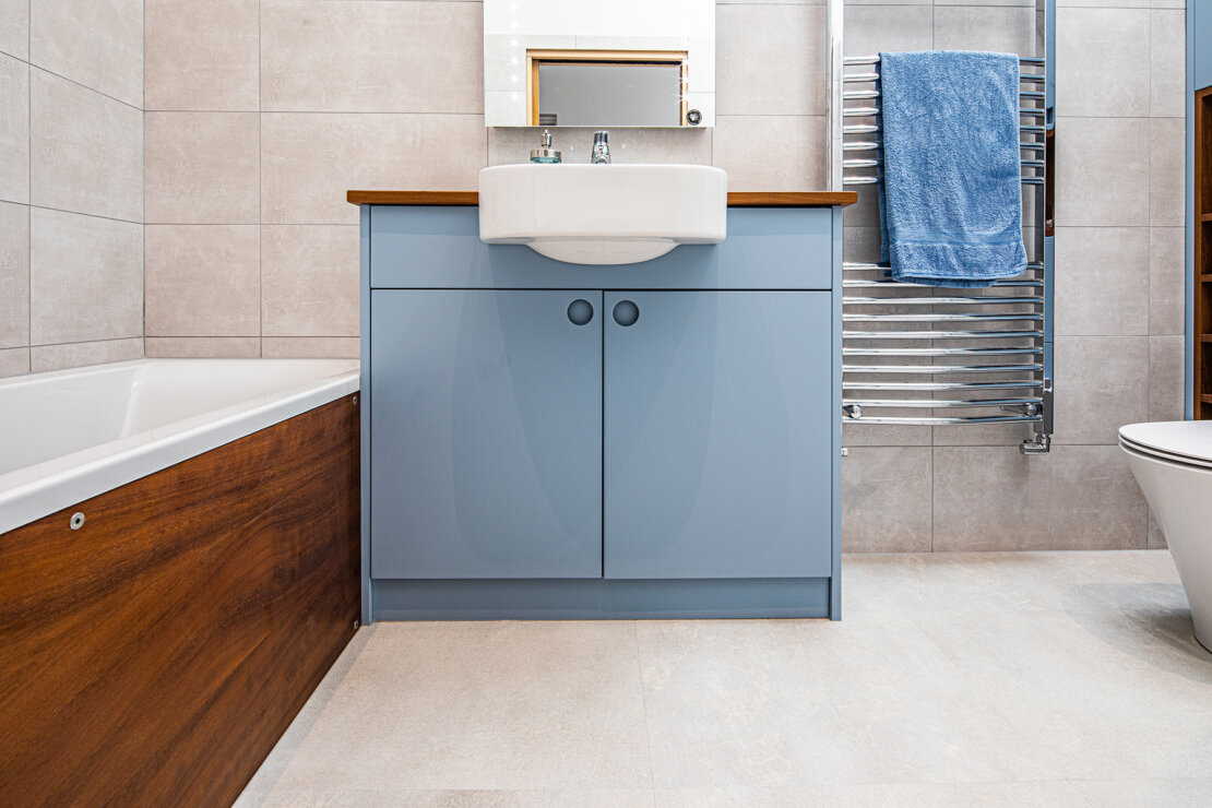 Under sink unit next to bath with reclaimed iroko panel