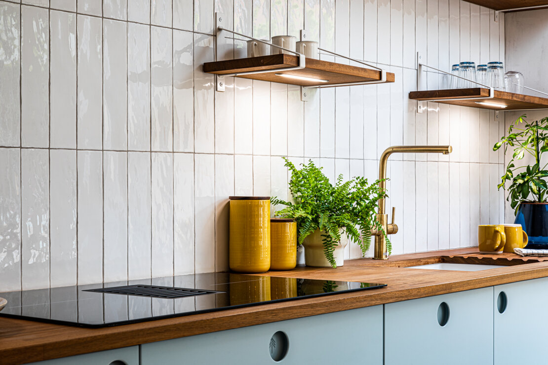 white tiled kitchen wall with timber worktop and blue cabinets
