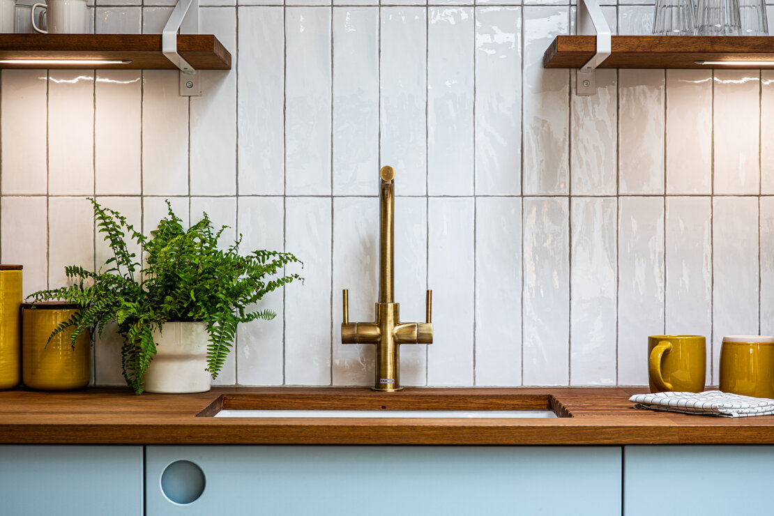brass tap in timber worktop in front of vertical white tiled wall