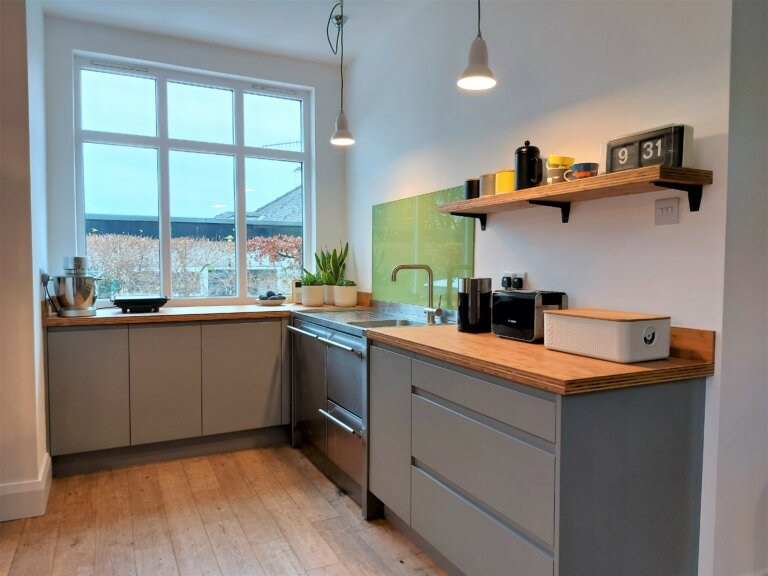 grey l-shaped kitchen with stainless steel sink and bamboo worktop